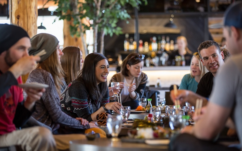 Group of people enjoying apres sushi at Japanese restaurant Kuma Yama, Lake Louise Ski Resort, Banff National Park.