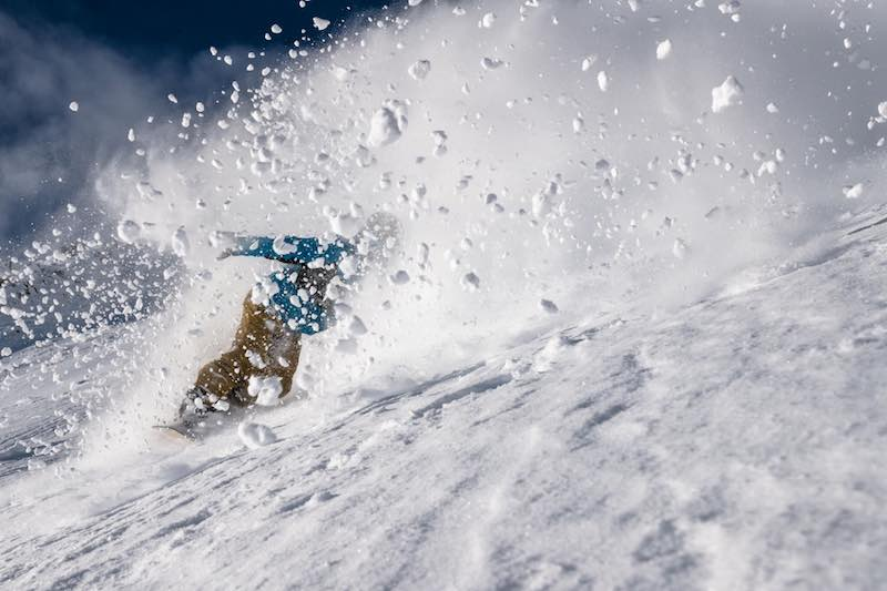 Snowboarder ripping up powder