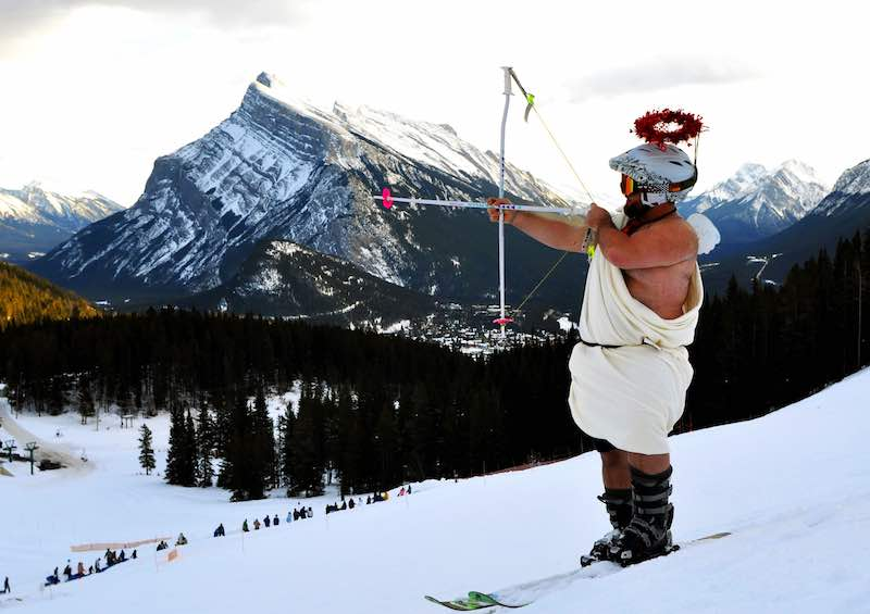 Cupid skis the slopes of Mt. Norquay, Mt. Rundle in the background, Banff National Park.