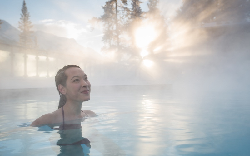 Woman enjoys the natural thermal waters at the Banff Upper Hot Springs, Banff National Park, Canada.