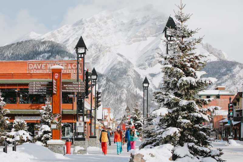 Group of skiers walks down Banff Avenue in winter with ski gear.