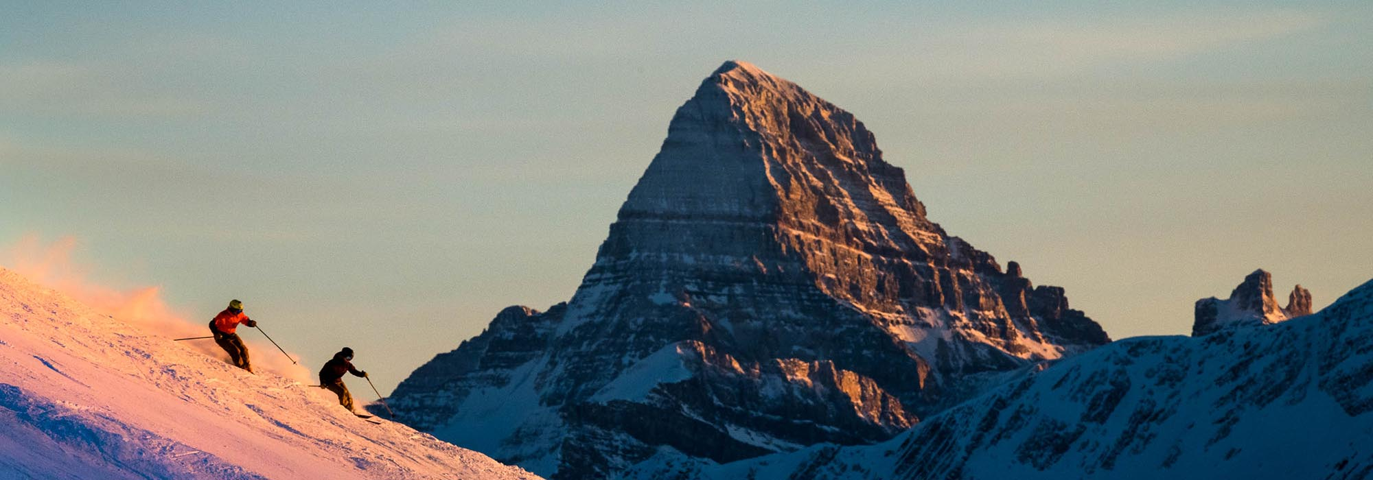 Skiers at Banff Sunshine Village with Mt. Assiniboine in the background, photo by Reuben Krabbe.
