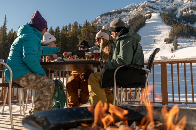 Group of skiers and snowboarders enjoy nachos on a patio with firepit at Mt. Norquay, Banff National Park.