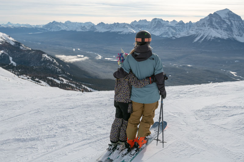Adult and child skiers take in view of Mt. Temple at Lake Louise Ski Resort, Banff National Park.