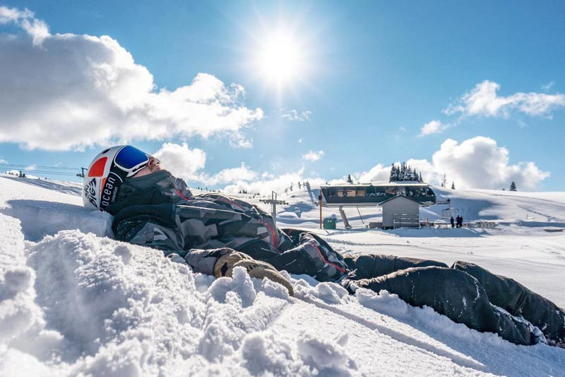 Skier lays in a field of early season snow at Sunshine Village, Banff National Park.
