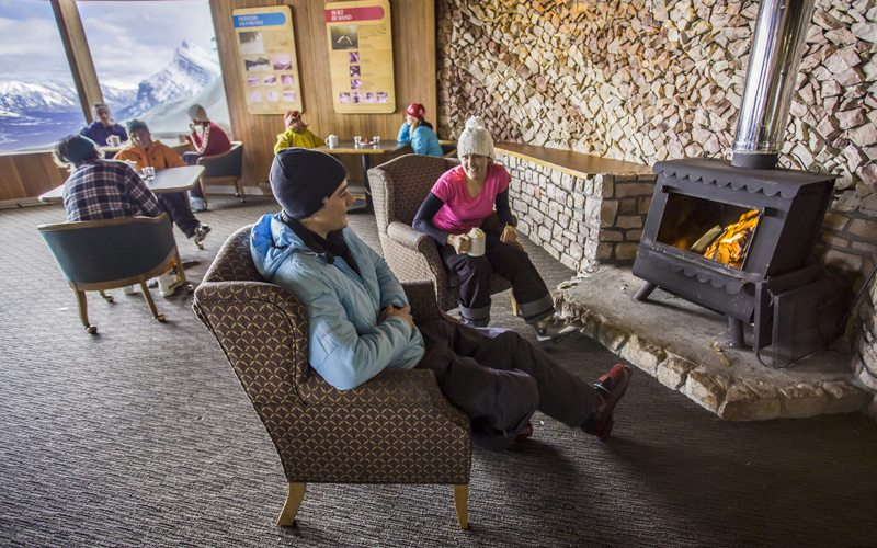 Warm up with an indoor break at an on-mountain lodge. Photo: Mt Norquay's Cliffhouse Bistro by Paul Zizka.