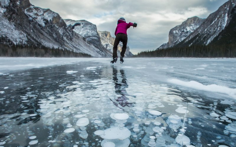 Ice skating on Lake Minnewanka is a spectacular early winter adventure. Photo: Paul Zizka.