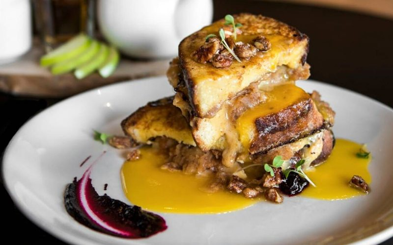 Juniper Bistro's apple and brie stuffed brioche French toast is a delicious way to start your ski day. Photo by @juniperbanff on Instagram.