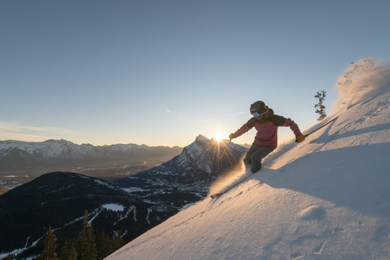 Skier at Mt. Norquay ski resort, Mt. Rundle in the background.