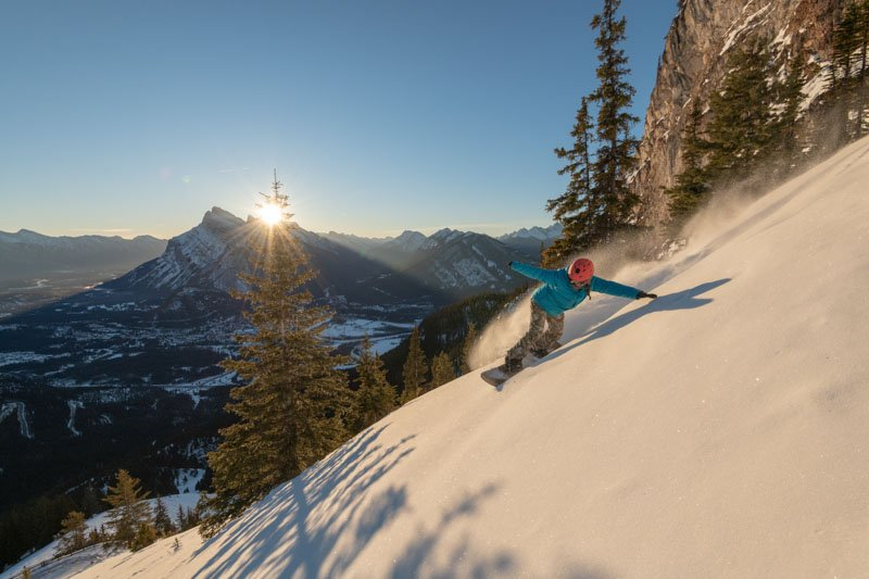 Snowboarder at Mt. Norquay ski resort, Mt. Rundle in background.