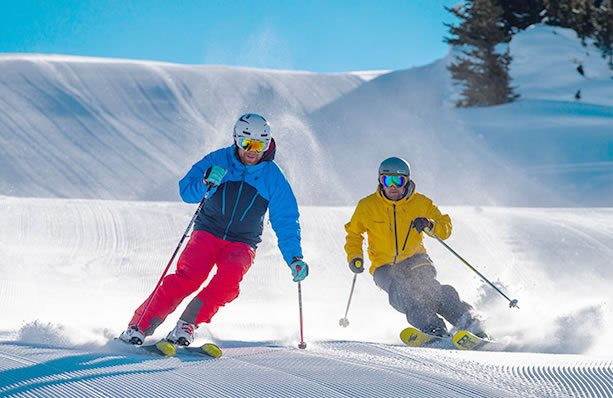 Two skiers on groomers.
