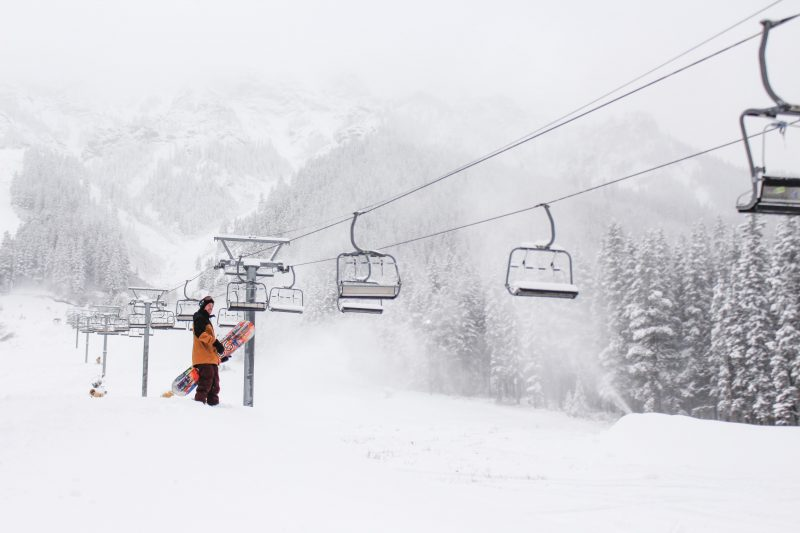 Snowboarder by chair lift at Mt. Norquay.