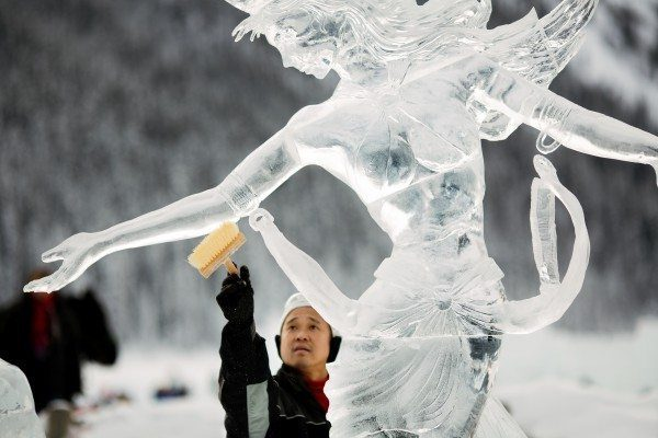 Ice artist polishes an ice sculpture as part of the Lake Louise Ice Magic Festival.