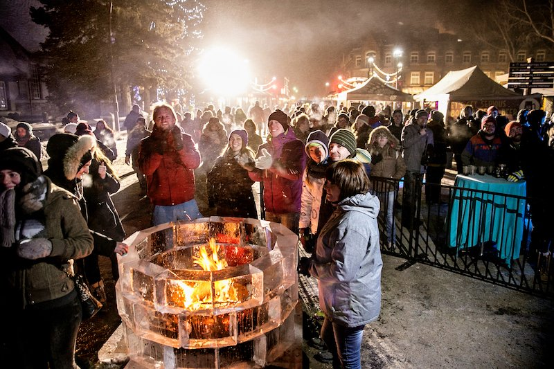 Snow Days attendees warm up at an outdoor bonfire at Snow Days festival in Banff, Alberta.