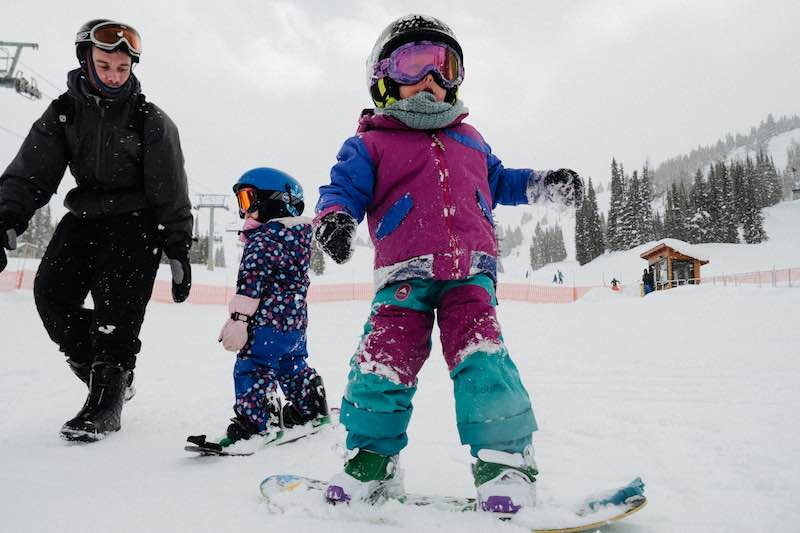 Kids snowboard on the magic carpet at Banff Sunshine Village, Banff National Park.