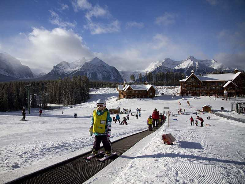 Kids go up the magic carpet at Lake Louise Ski Resort, Banff National Park.