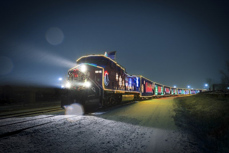 The CP Holiday Train journeys through the night, illuminated in Christmas lights.