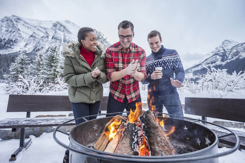 Three people warm up by an outdoor campfire at Fairmont Chateau Lake Louise, Banff National Park.