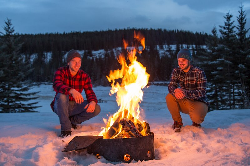 Two people crouch near an outdoor winter campfire at Cascade Ponds, Banff National Park.