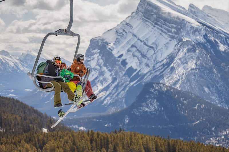 Family riding chairlift at Mt. Norquay ski resort in Banff National Park.