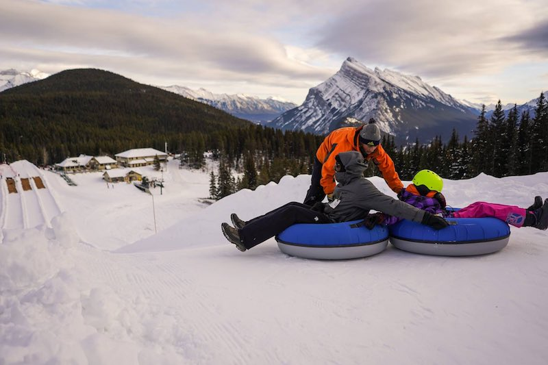 Family snow tubing at Mt. Norquay ski resort in Banff National Park.