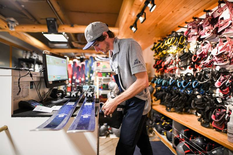 Shop technician fits ski boots to a pair of rental skis at the SkiBig3 Adventure Hub in Banff National Park.