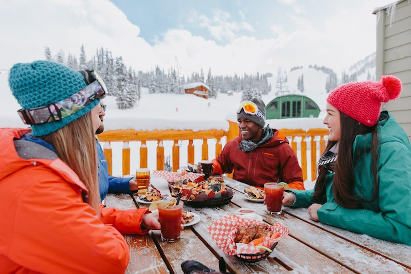 Four friends enjoy wings and apres drinks at Mad Trappers Patio at Banff Sunshine Village, Banff National Park.
