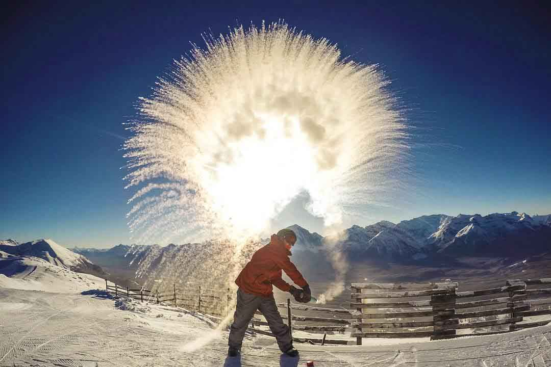 Creating ice spray with warm water in cold temperatures at Lake Louise Ski Resort, Banff National Park.