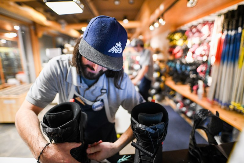 Gear technicians at the SkiBIg3 Adventure Hub fit snowboard boots to a snowboard in Banff National Park.
