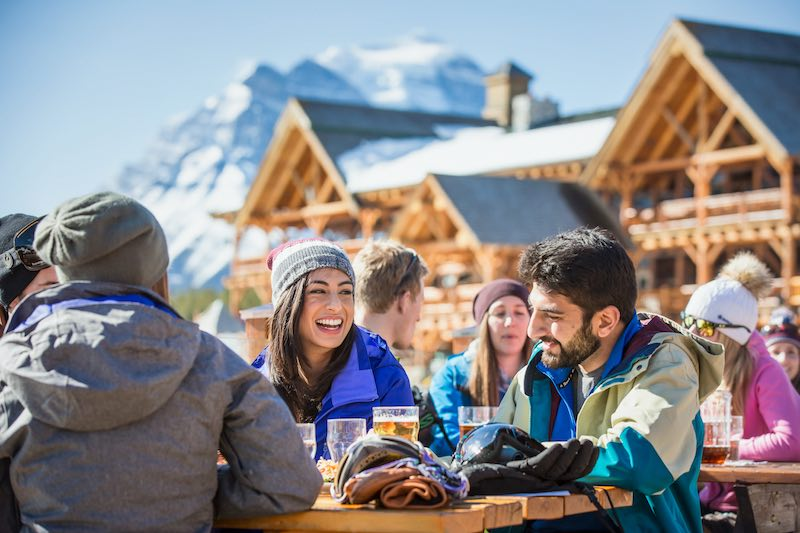 A group of friends enjoy pints on the Kokanee Kabin Patio during spring skiing at Lake Louise Ski Resort, Banff National Park.