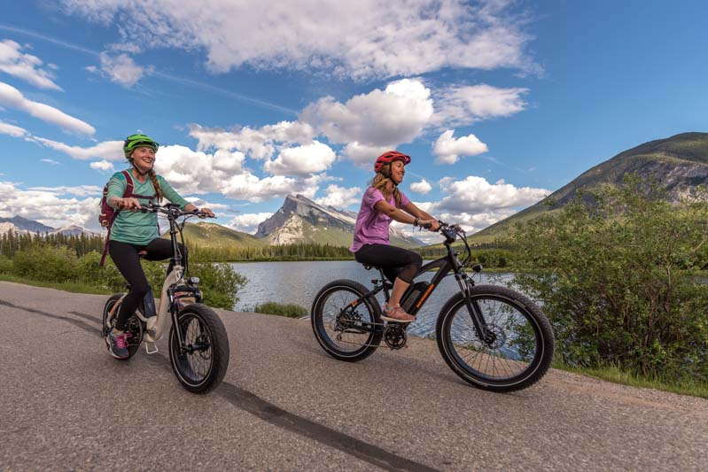 Two cyclists ride their e-bikes along Vermillion Lakes Road, Banff National Park, view of Mt. Rundle in the background.