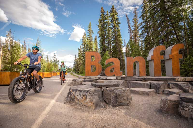 E-bike riders pedal past the Banff West entrance sign on Mt. Norquay road, Banff National Park.