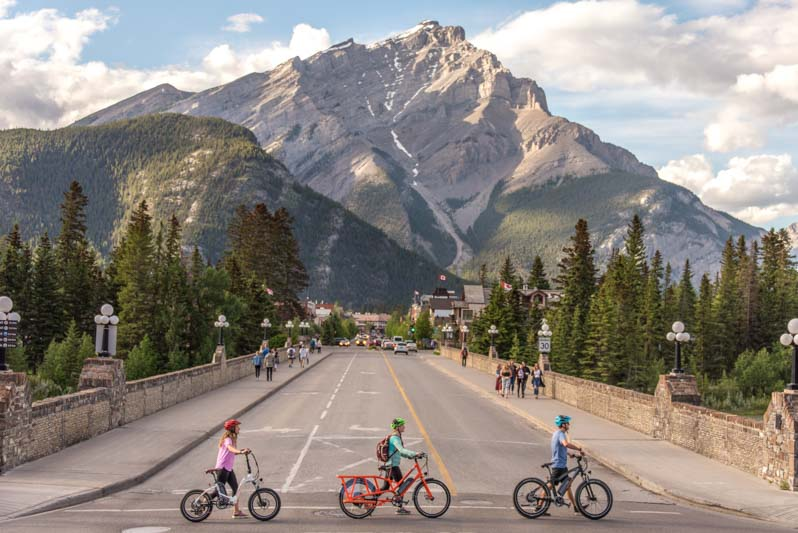 Cyclists walk their e-bikes across a pedestrian crosswalk on Banff Avenue, view of Cascade Mountain in the distance, Banff National Park.