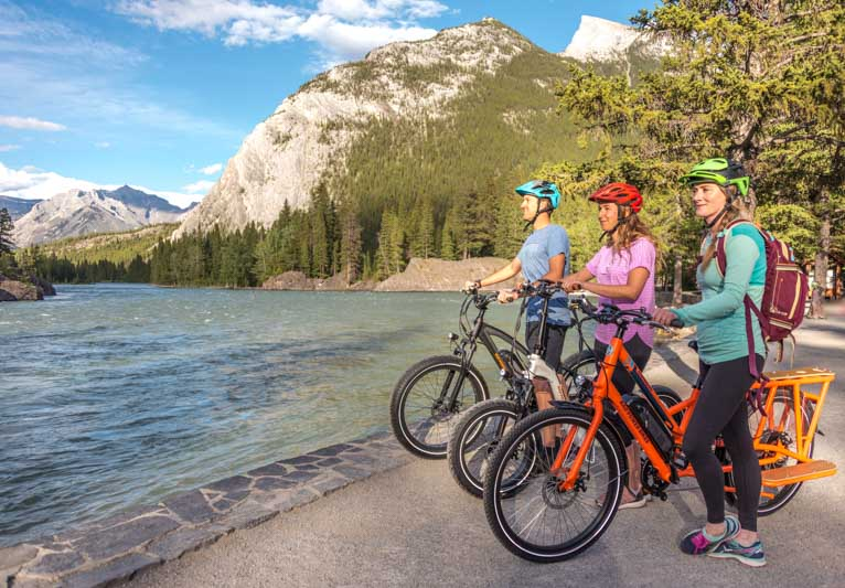 E-bike riders take in the view at Bow Falls near the Golf Course Road loop in the town of Banff, Banff National Park.