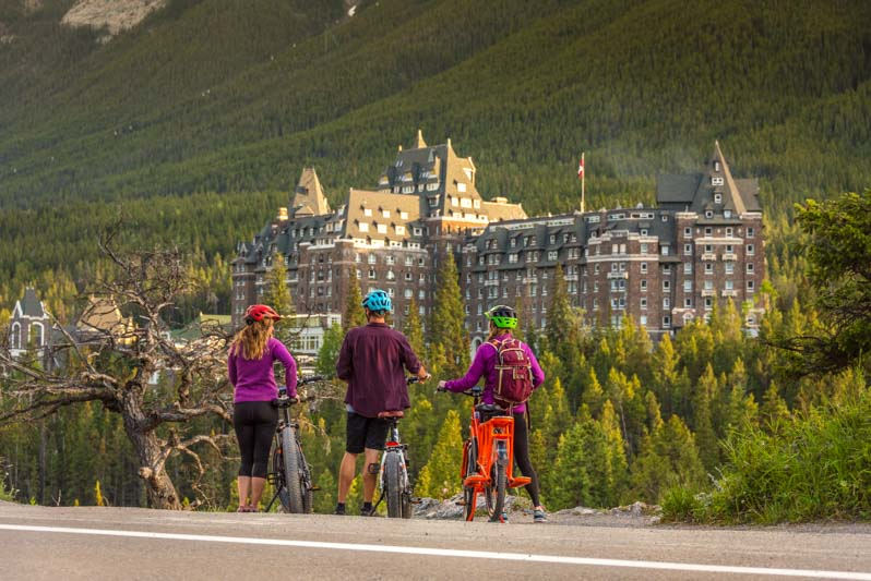 Three e-bike cyclists take in the view of the Fairmont Banff Springs hotel from Surprise Corner along the Tunnel Mountain Road Loop, town of Banff, Banff National Park.