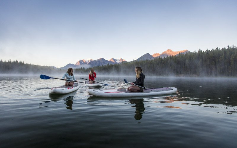 Three people sit on stand-up paddleboards on Herbert Lake, Banff National Park.