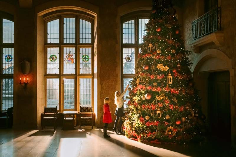 Children decorating Christmas tree at Fairmont Banff Springs hotel, Banff National Park.