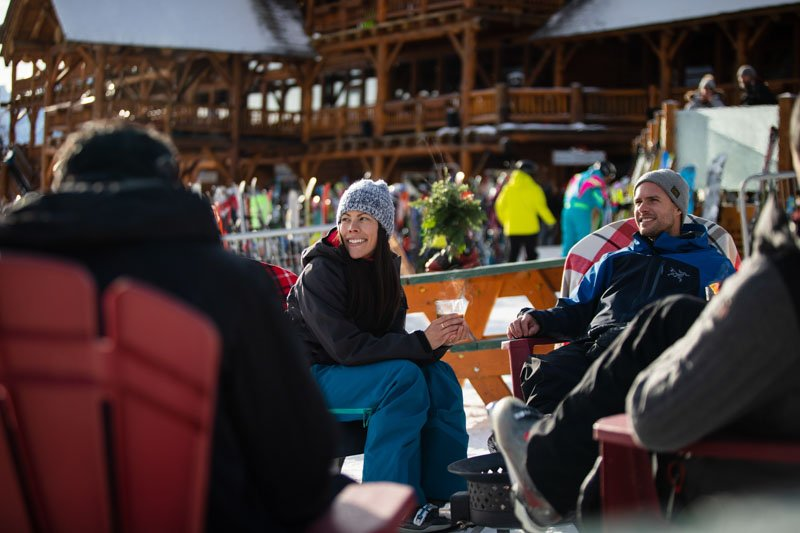 Couple watching athletes cross the finish line at Lake Louise World Cup, on Kokanee Kabin deck.