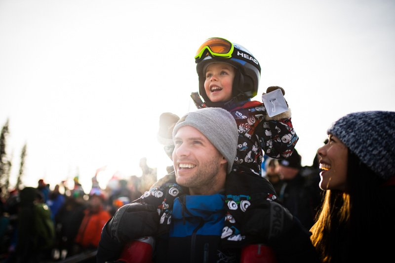 Father with daughter on shoulders watching World Cup athletes from the VIP fan cheering zone.