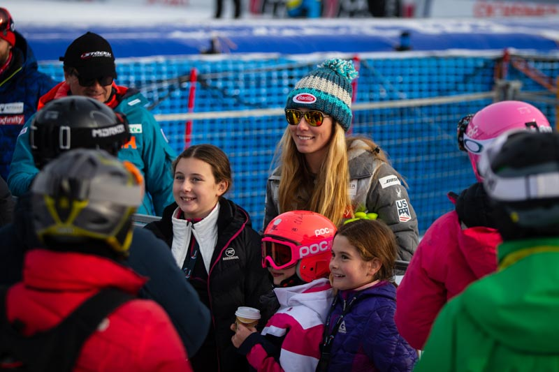Mikaela Shiffrin at Lake Louise Alpine Ski World Cup signing autographs with kids in the fan cheering zone.