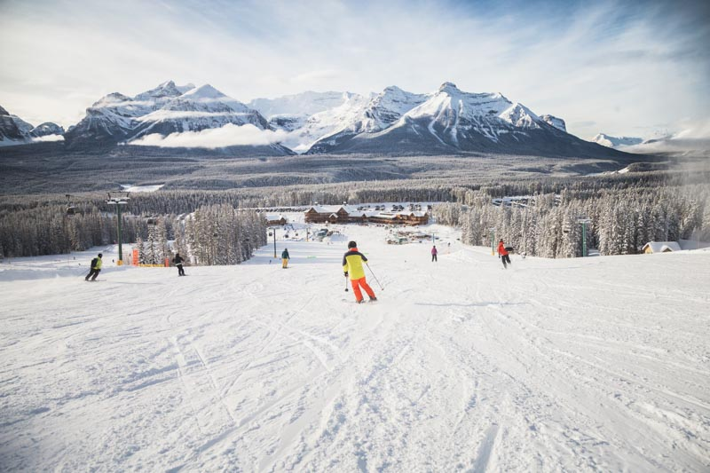 Skier at Lake Louise Ski Resort, Banff National Park. Mt. Temple and Lodge of Ten Peaks in background.