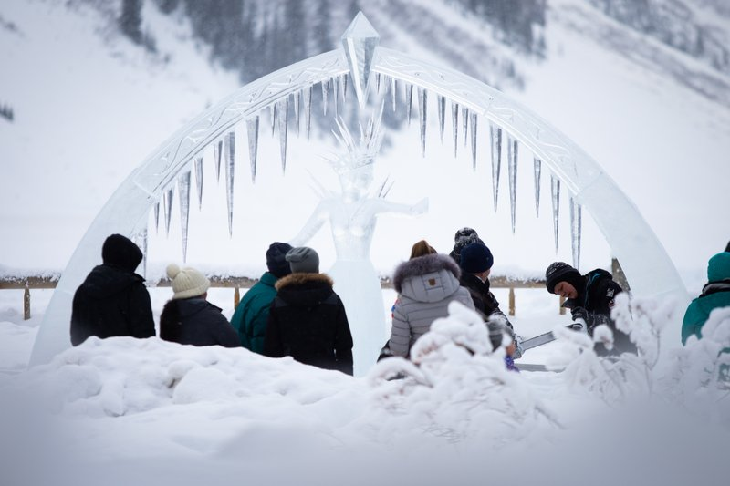 Crowds watch a sculptor create and ice sculpture at Ice Magic event in Lake Louise, Alberta.