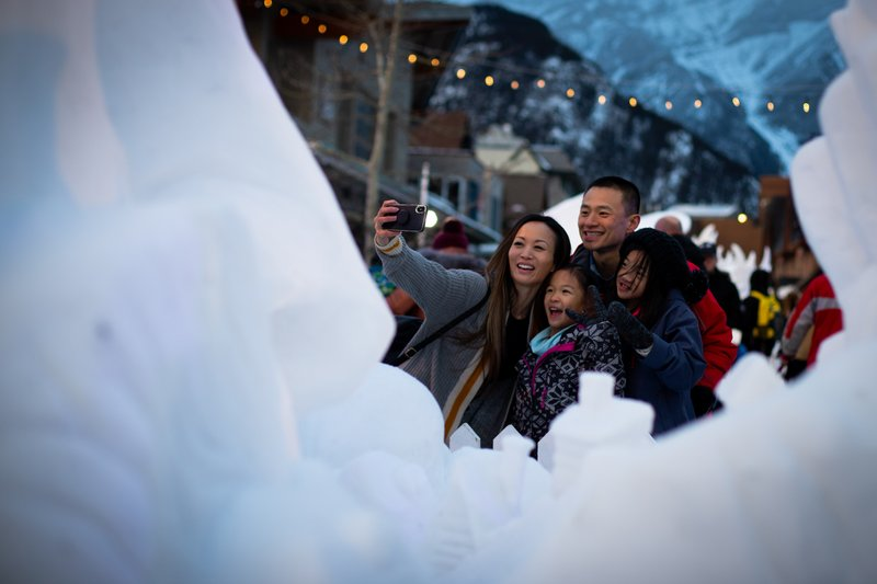 Family taking a selfie next to a snow sculpture on Bear Street, Banff, Alberta during SnowDays.