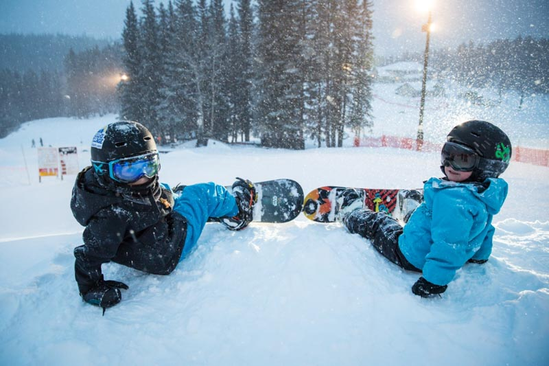 Two boys snowboarding at Mt. Norquay, Banff National Park.