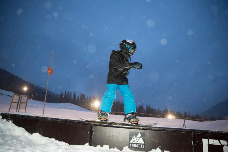 Boy snowboarding during night skiing at Mt. Norquay, Banff National Park.
