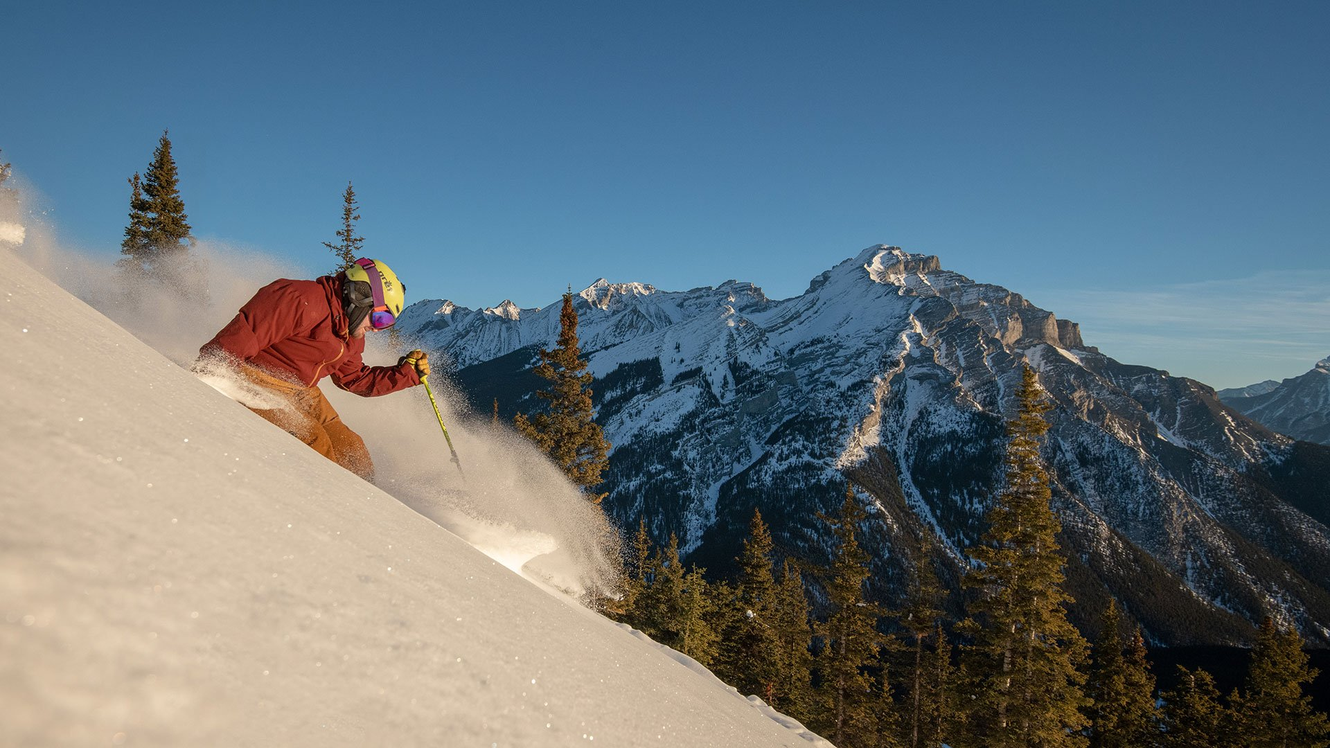 Skier at Mt. Norquay ski resort, Mt. Rundle in the background. Banff National Park.