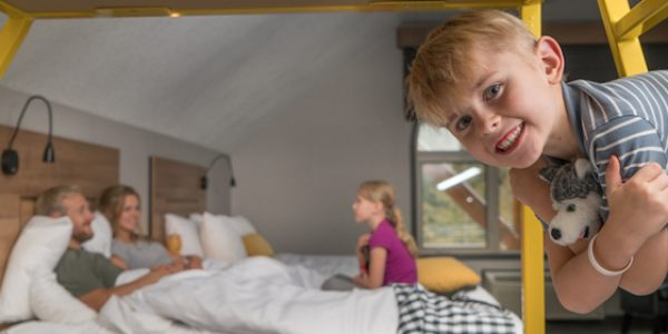 Interior shot of child on bunkbed in loft suite at CanAlta Lodge in Banff